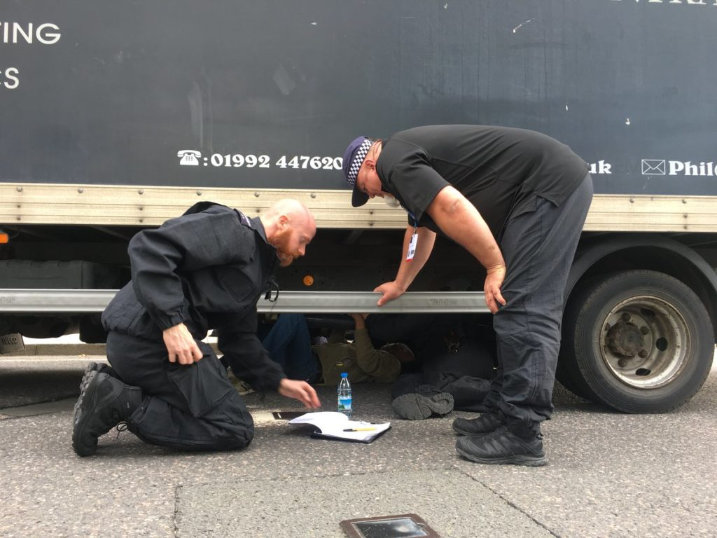 Police try to remove protester locked underneath an arms delivery truck.
