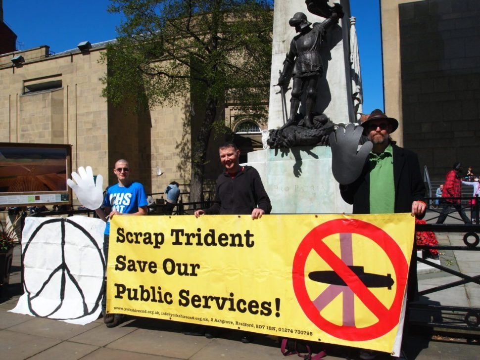 Image of Adam, Matt and Billy standing in front of the war memorial outside Leeds Art Gallery with a CND Logo banner and a Yorkshire CND banner which says 'Scrap Trident Save Our Public Services'.