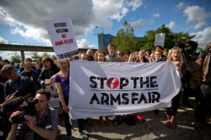 "Image of protestors holding a banner that reads ""Stop the Arms Fair"""