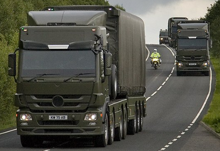 Image of miltary trucks on a public road with a police escort