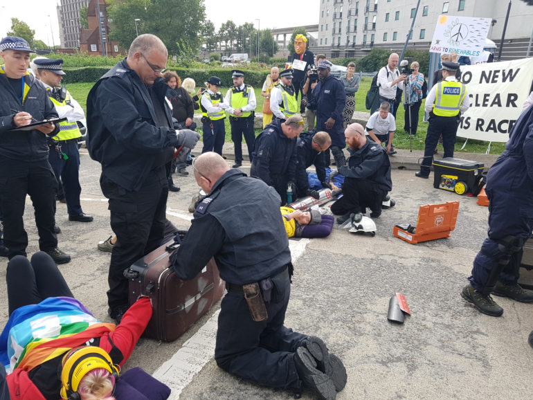 Photo showing police cutting teams removing anti-nuclear protesters