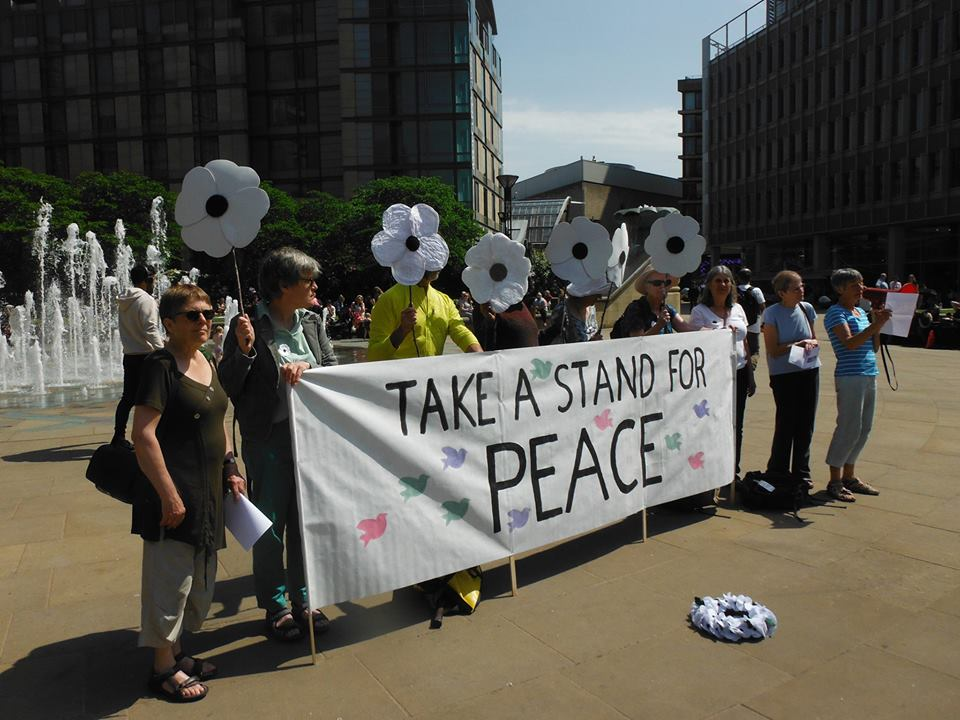 women with huge white poppies remember conscientious objectors in sheffield